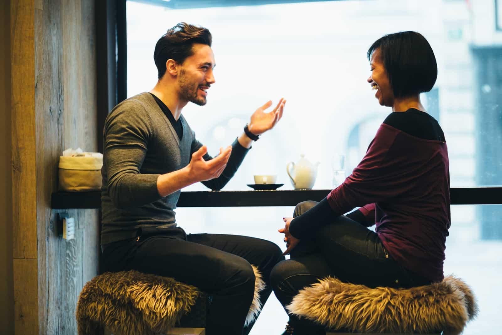 un homme et une femme sont assis sur un tabouret en buvant du café et en riant