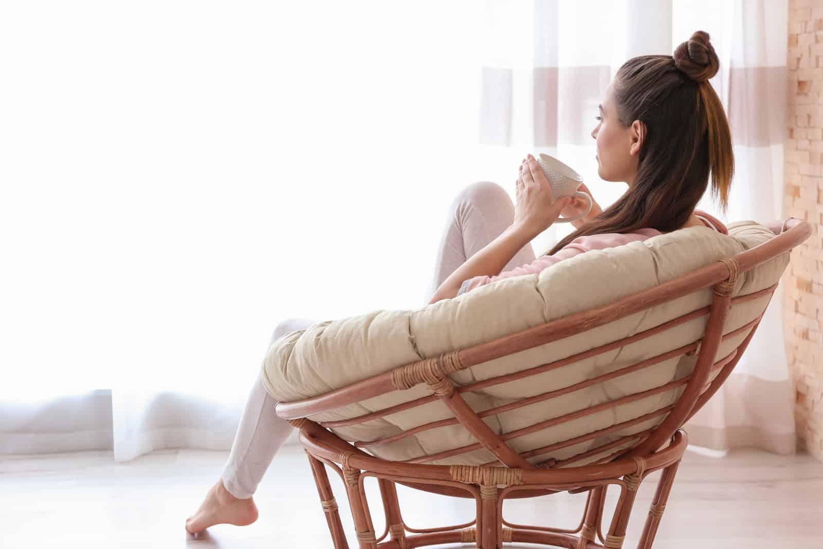 une femme assise dans un fauteuil, boire du café