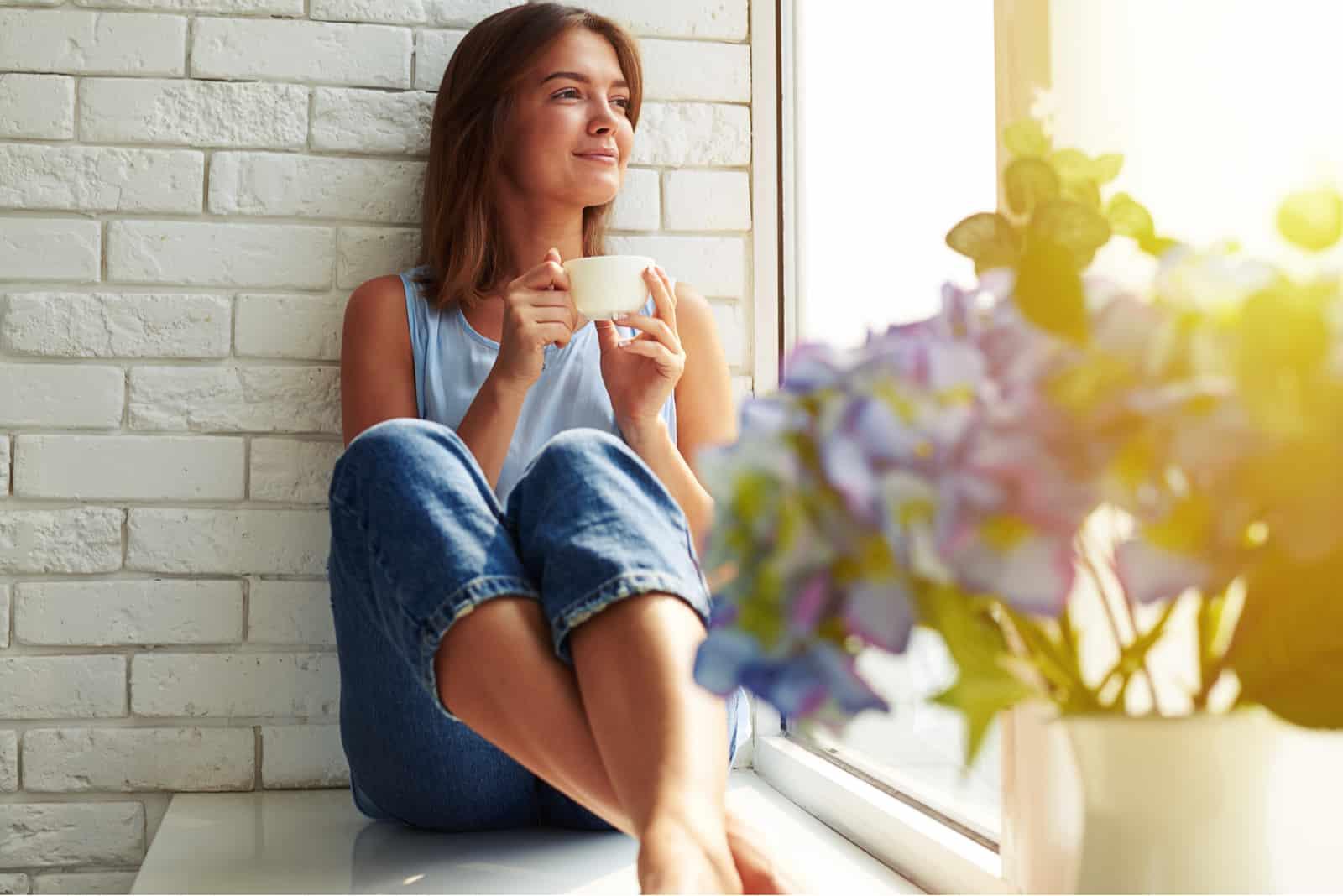 une femme assise près de la fenêtre, boire du café