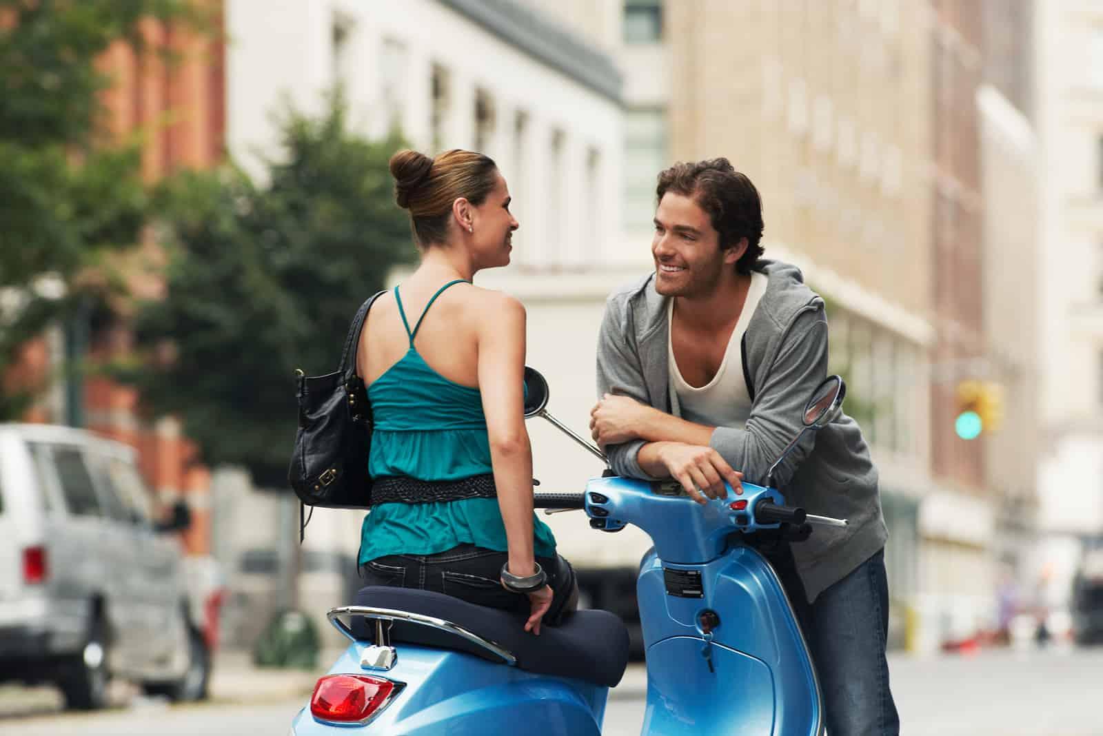 une femme assise sur une moto tout en parlant à un homme