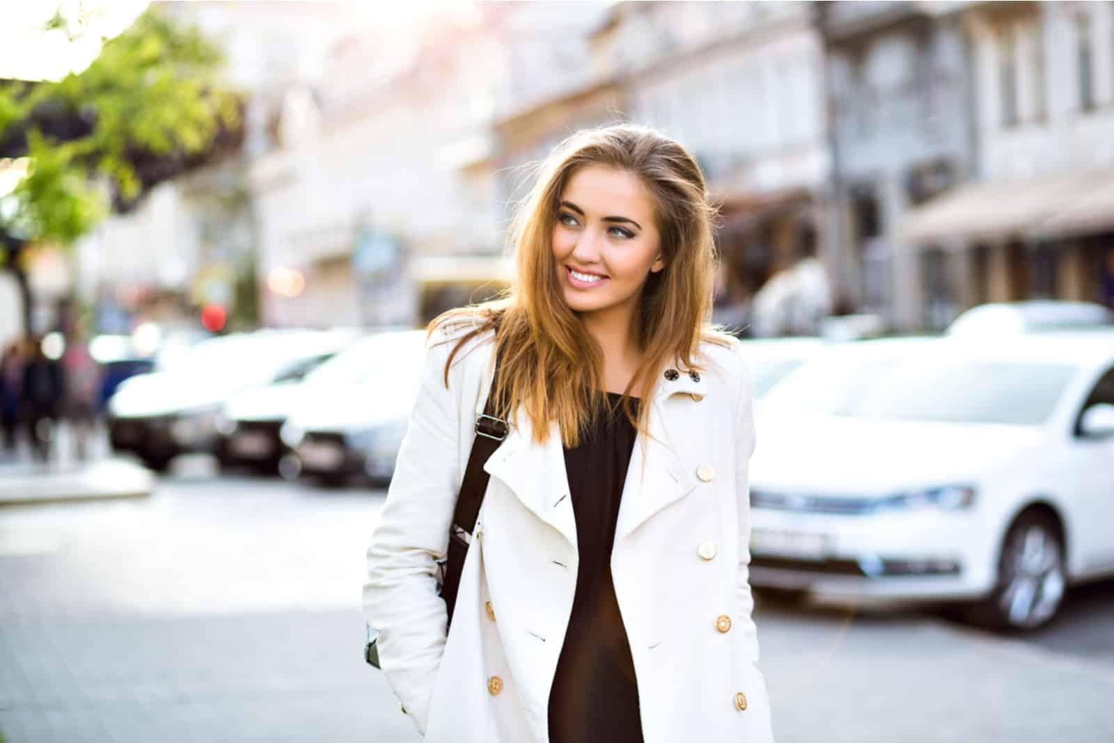 une femme aux cheveux bruns marche dans la rue