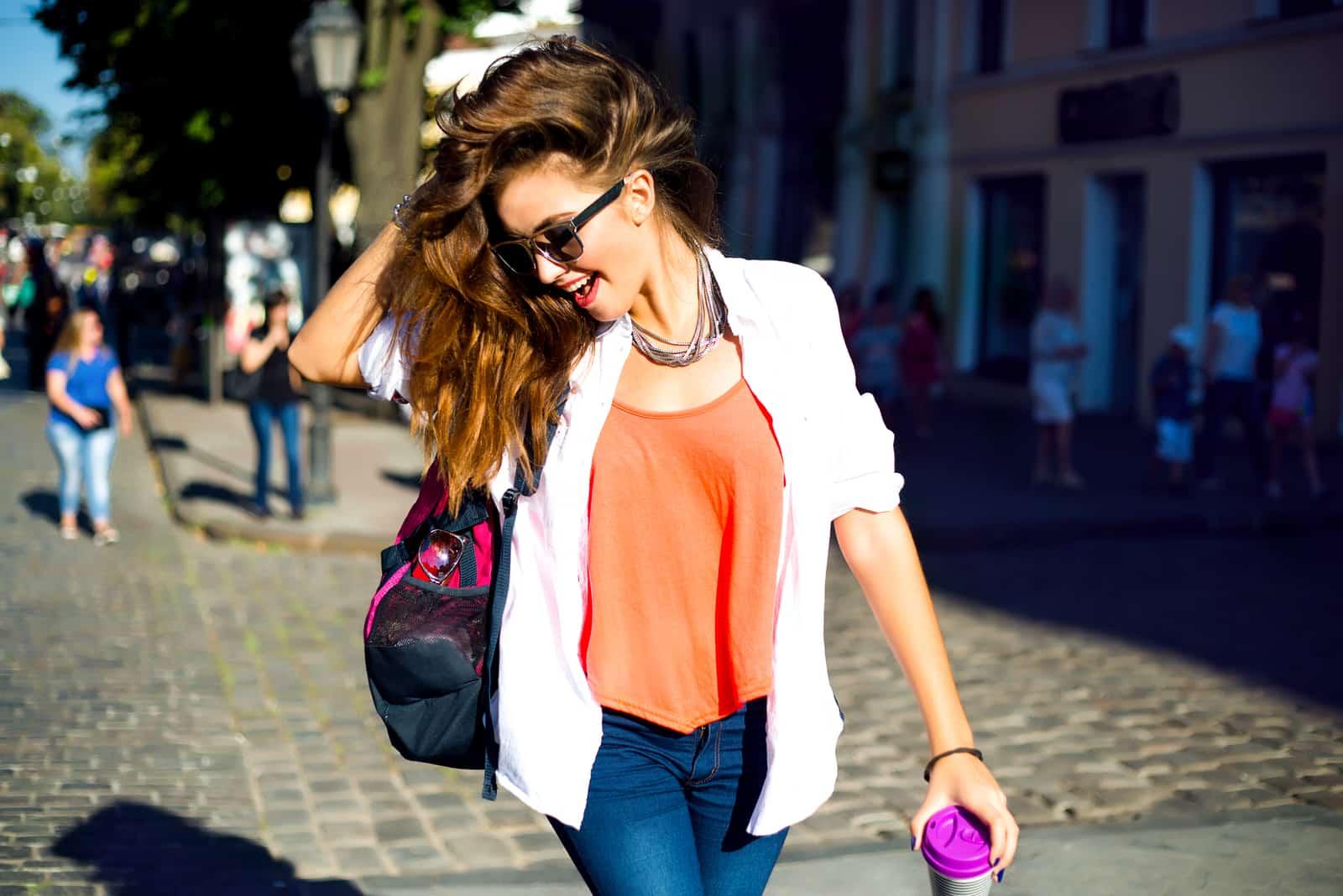 une femme aux longs cheveux bruns marche dans la rue et rit