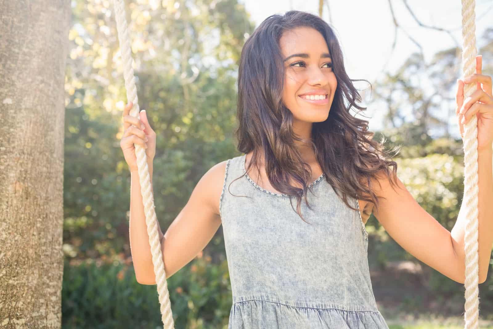 une femme aux longs cheveux bruns se balance