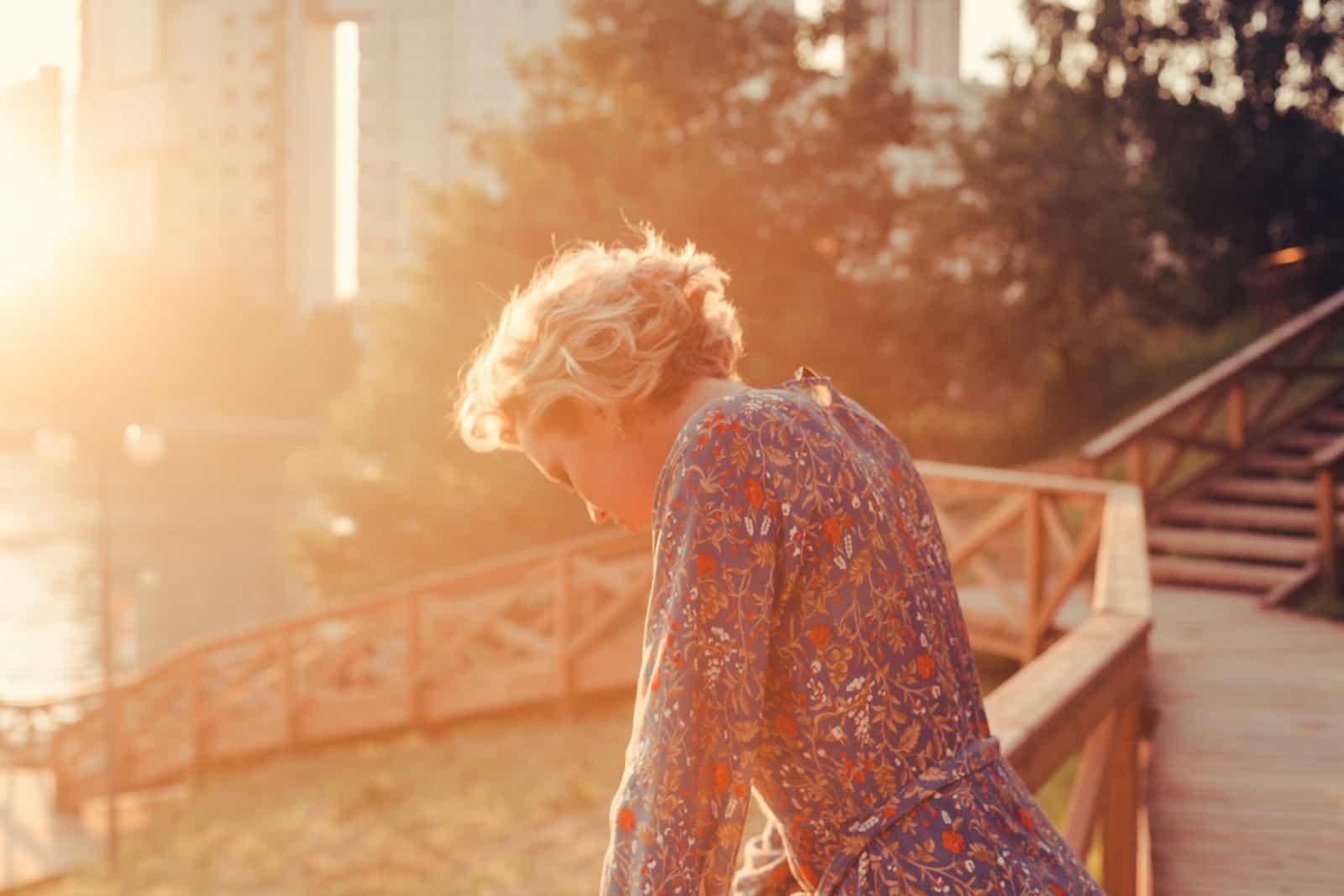 une femme avec la tête baissée se dresse sur un pont