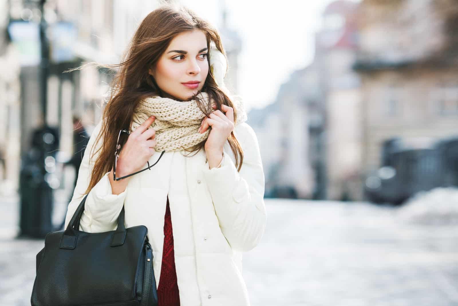 une femme avec une graisse autour du cou se tient dans la rue