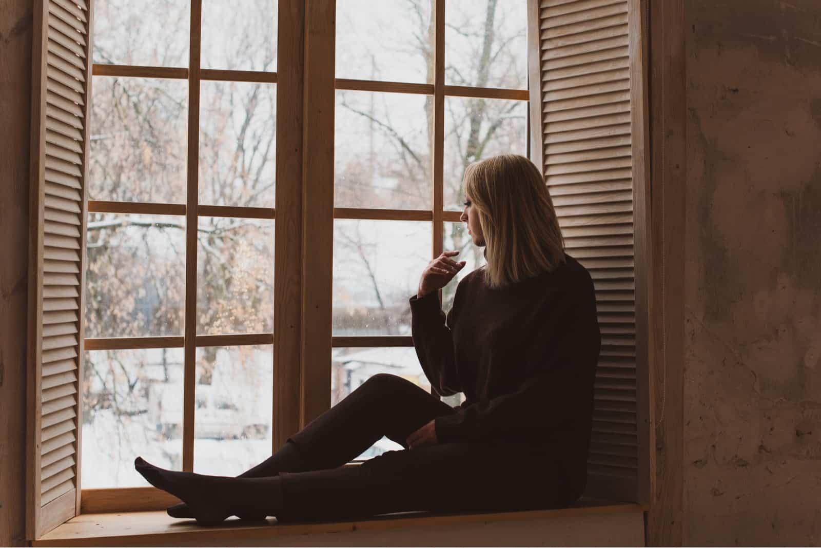 une femme blonde assise près de la fenêtre