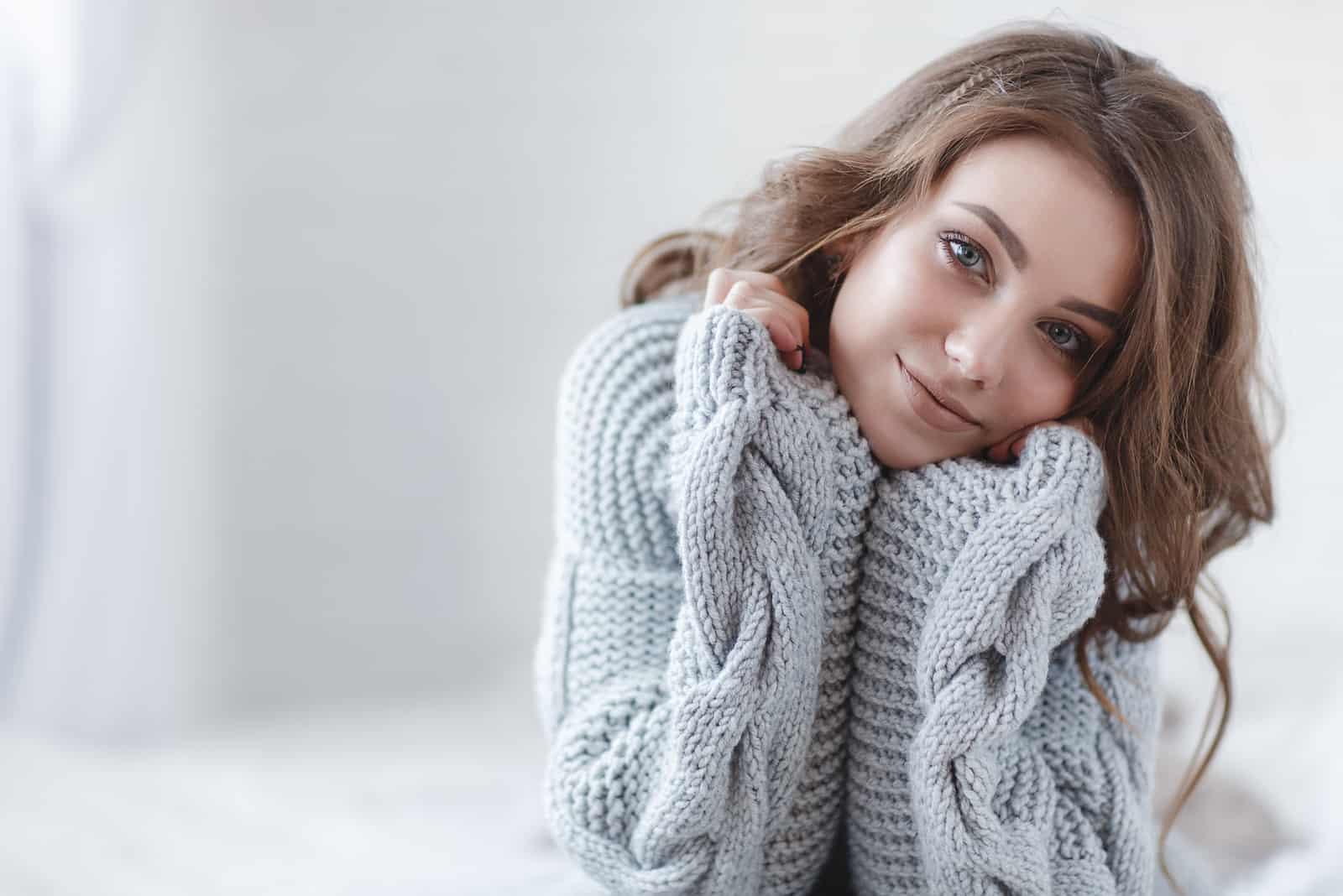 une femme dans un pull gris