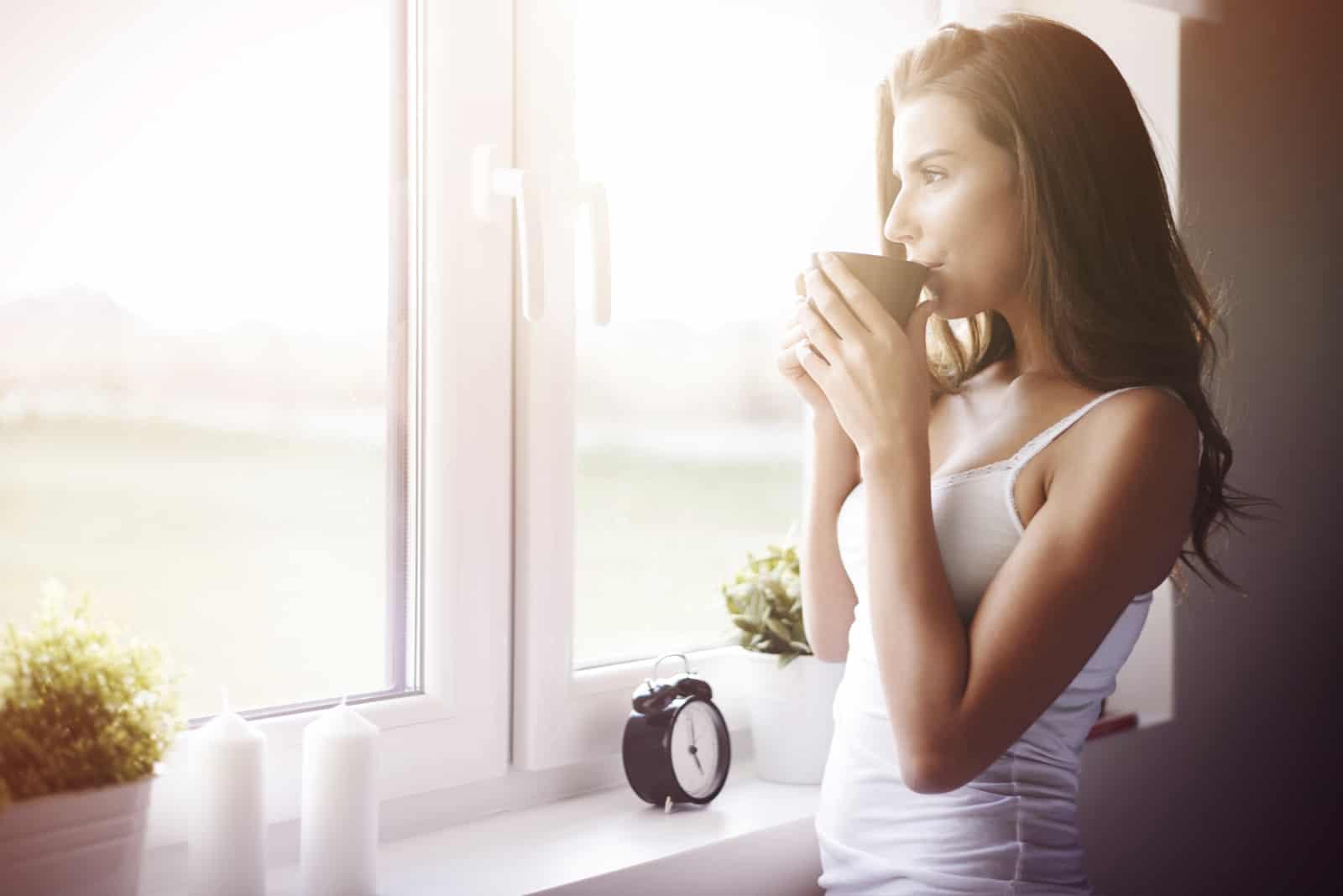 une femme debout près de la fenêtre, boire du café