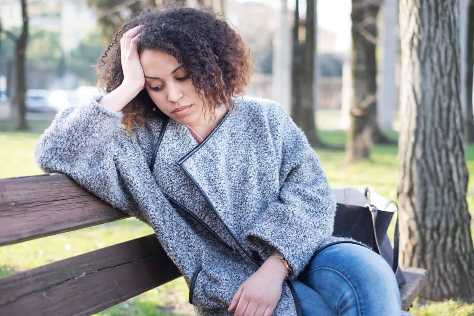 une femme imaginaire aux cheveux crépus est assise sur un banc