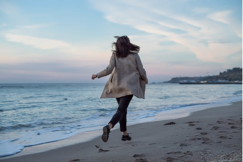 une femme qui traverse la plage