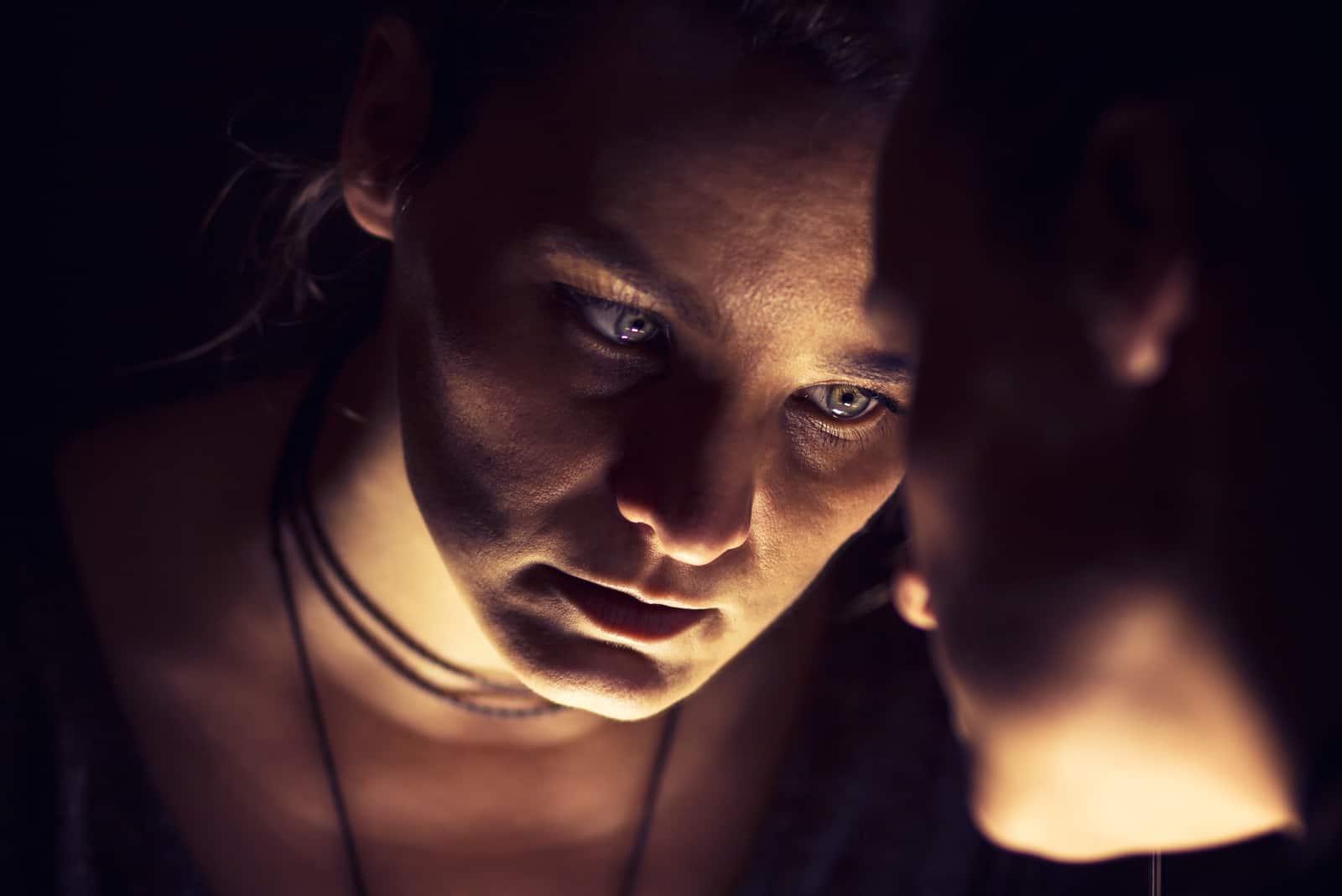 une femme triste dans le noir se regarde dans le miroir