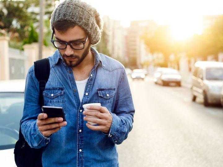 un homme debout avec un téléphone à la main