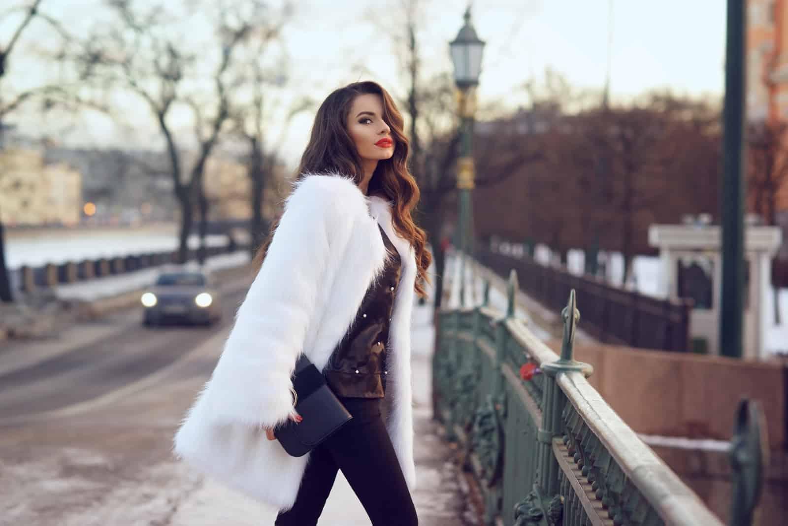 Belle jeune femme élégante marchant dans la rue