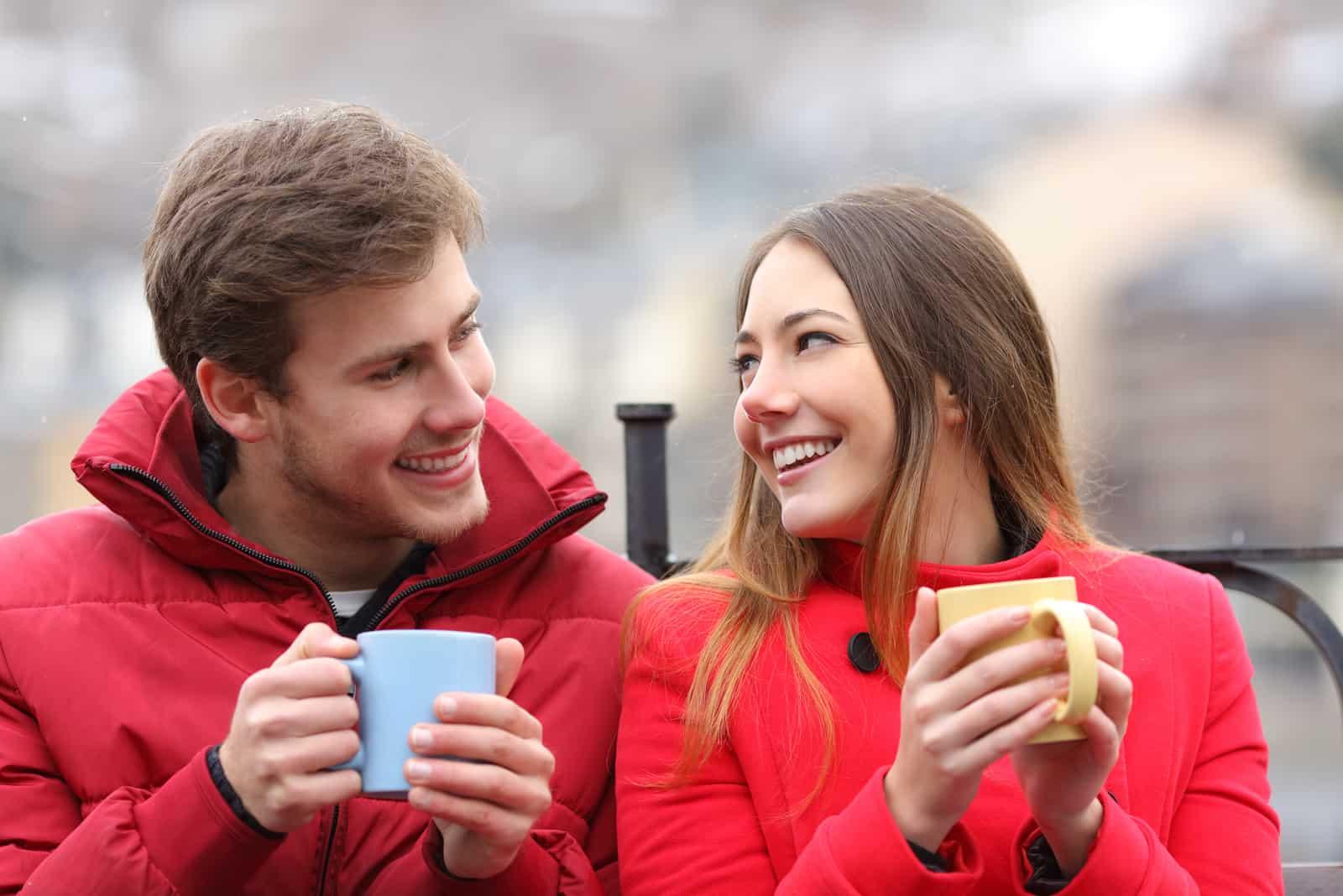 Couple parlant détendu assis sur un banc avec des tasses à café en hiver