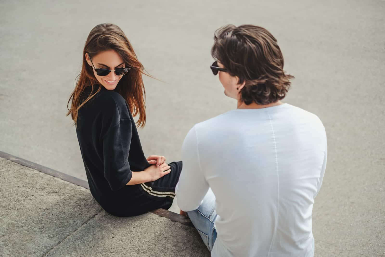 Fille timide assise sur un mur avec son petit ami et souriant pendant quil flirte avec elle