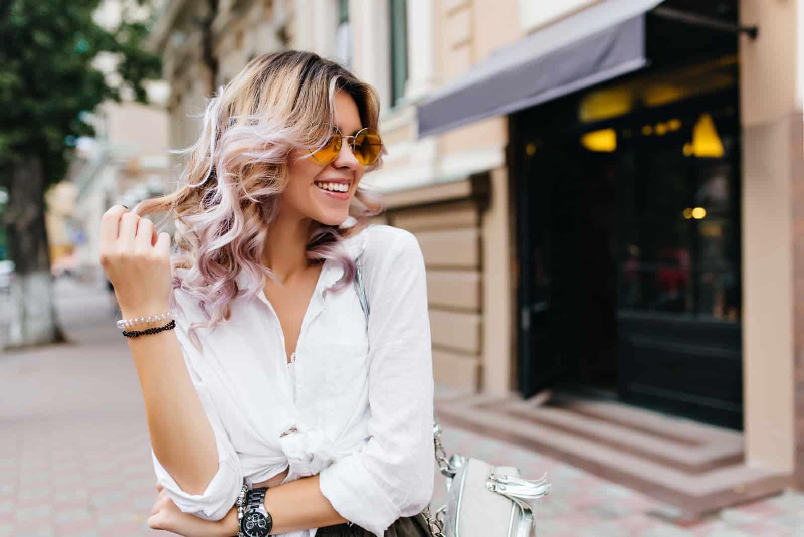 Jolie fille portant des lunettes de soleil et des bracelets jouant avec ses cheveux courts bouclés