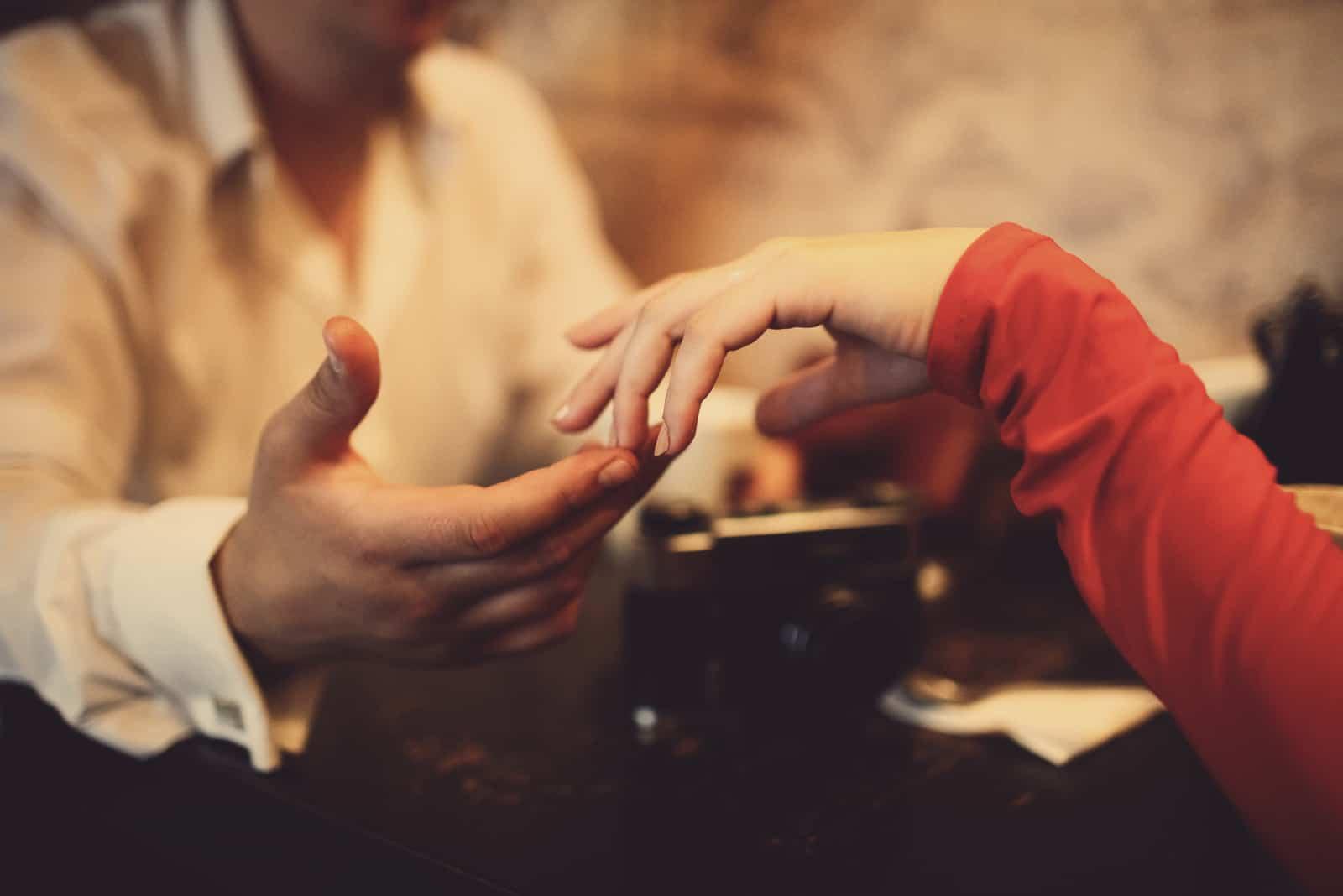 Le charmant couple amoureux se tient la main au restaurant
