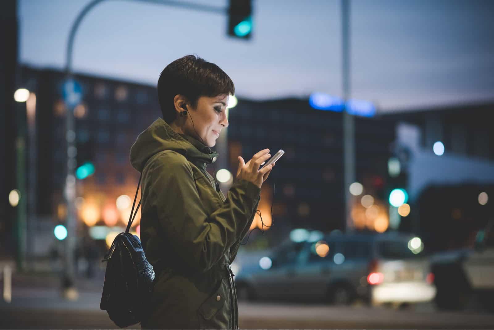 femme tenant un smartphone regardant vers le bas