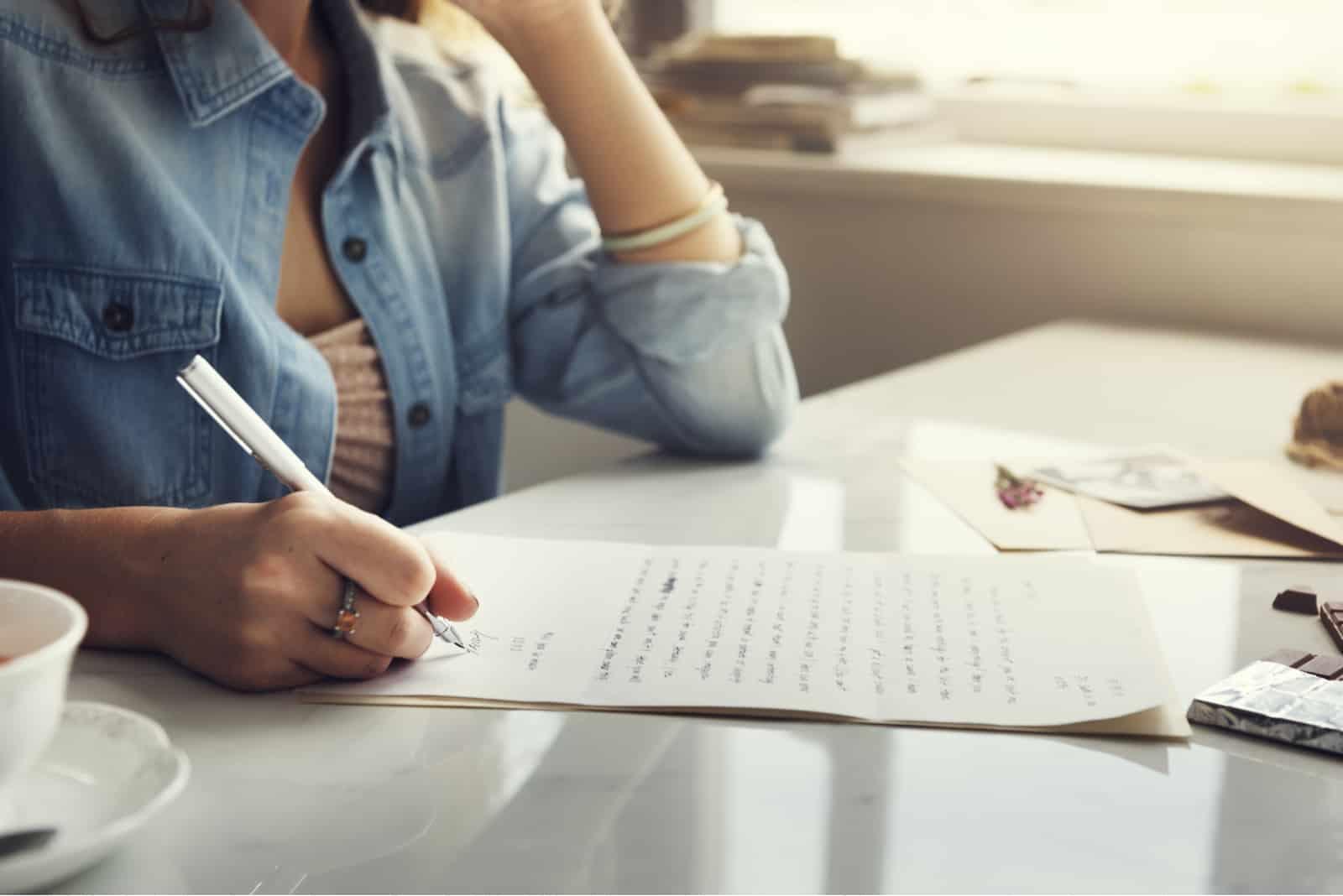 la femme s'assoit et écrit