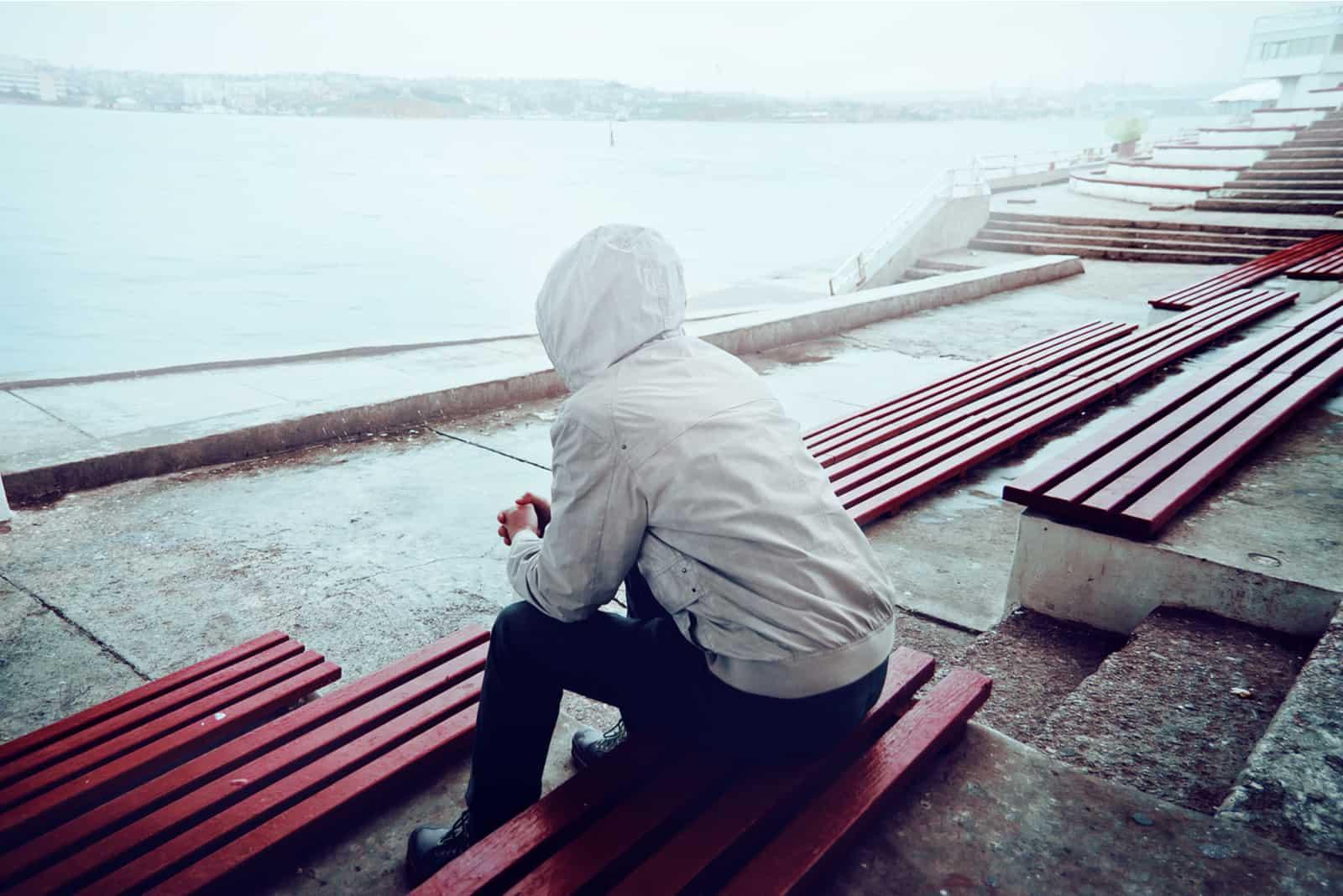 l'homme est assis sur un banc, le dos tourné