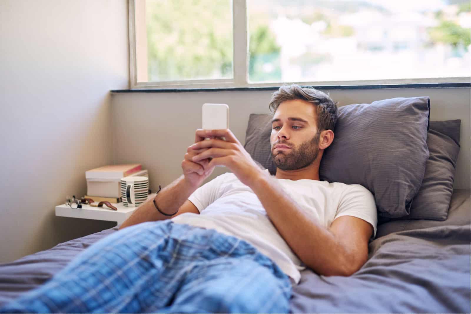 un bel homme en pyjama couché dans son lit et envoyer des SMS