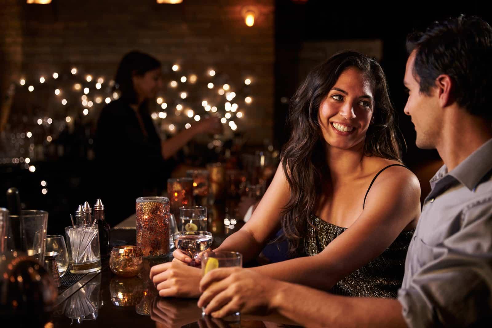 un couple d'amoureux heureux boit un verre au bar et flirte
