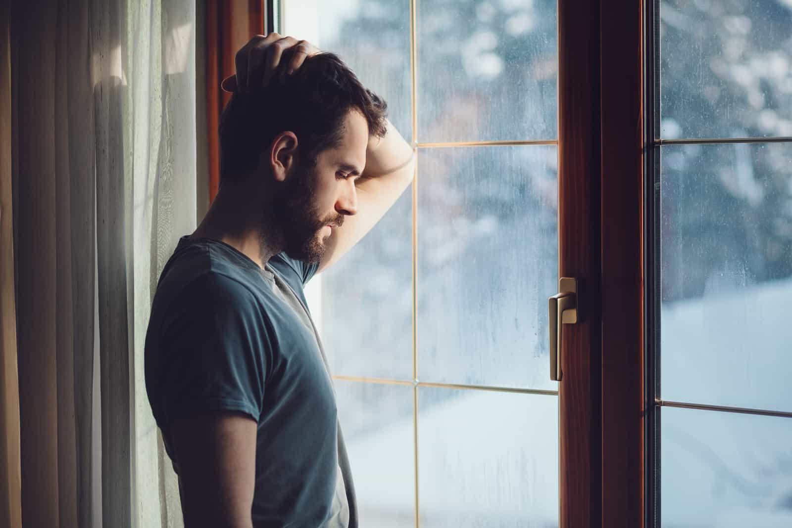un homme déçu se tient près de la fenêtre