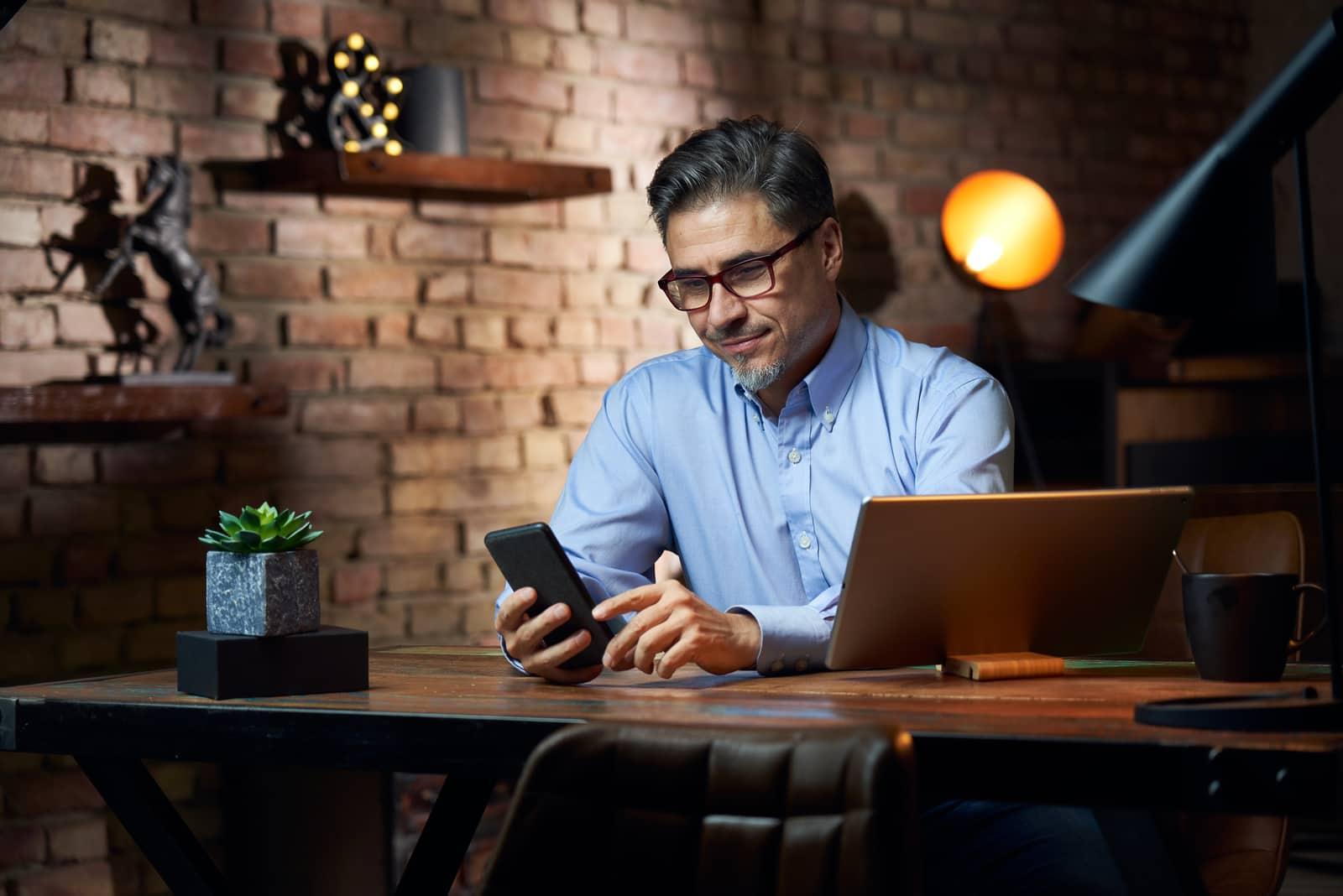 un homme est assis dans un bureau et écrit un message