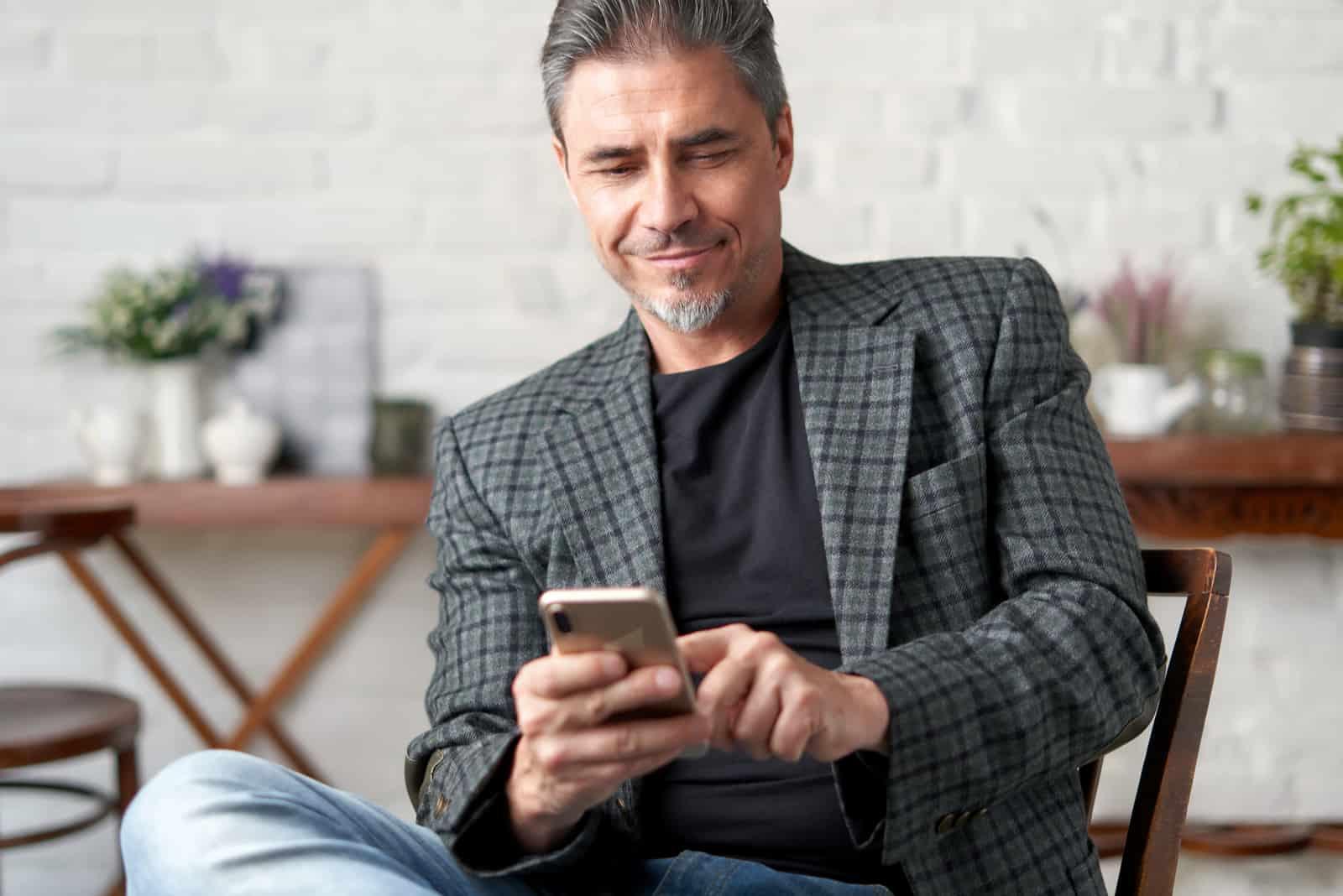 un homme est assis sur une chaise et une clé sur le téléphone