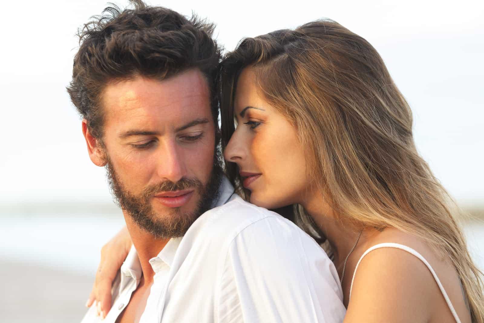 un homme et une femme étreignant sur la plage