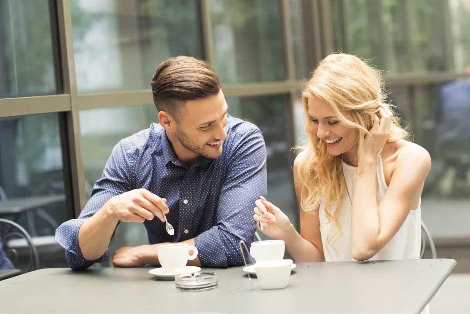 un homme et une femme s'assoient à une table et boivent du café