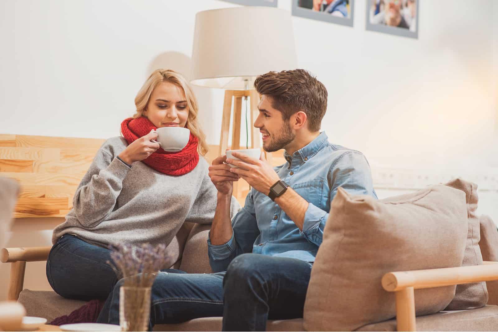 un homme et une femme sont assis sur le canapé en train de boire du café