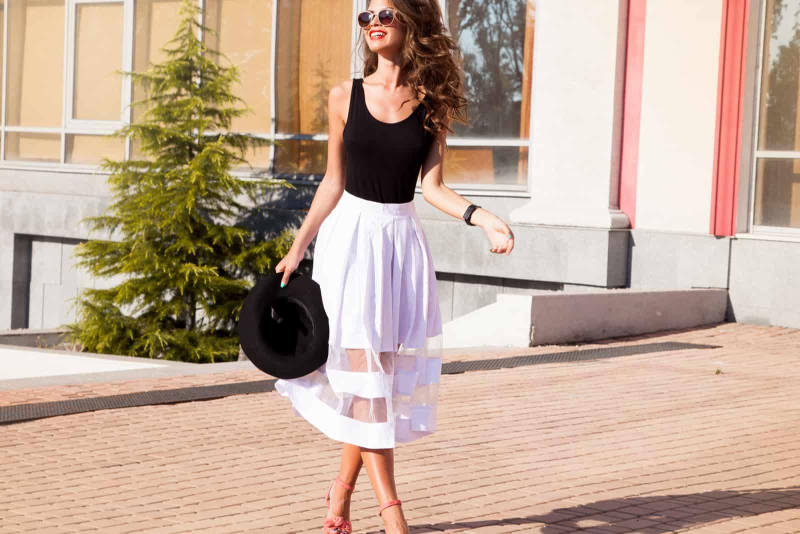 une femme aux longs cheveux bruns marche dans la rue
