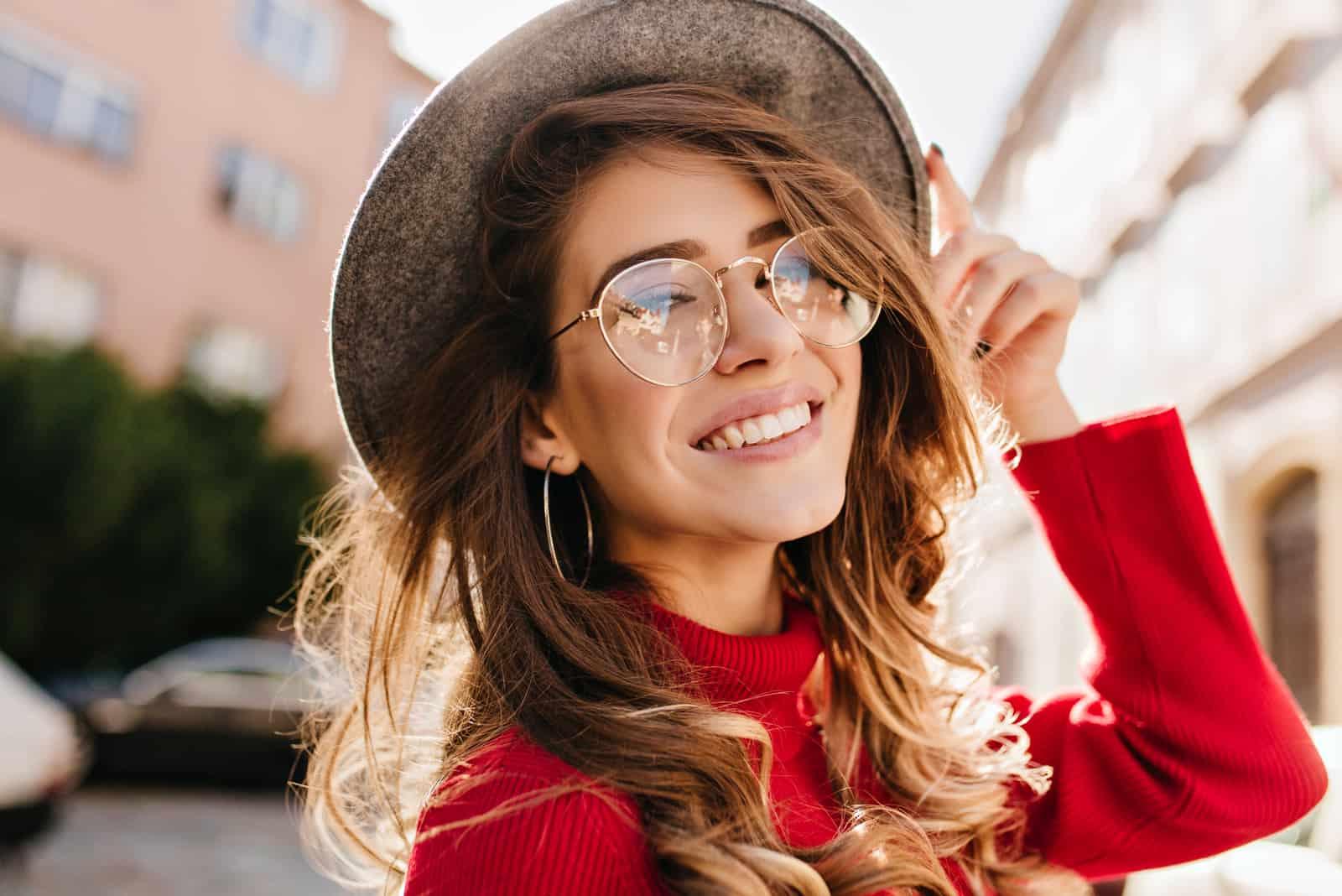 une femme avec un chapeau et des lunettes sur la tête rit