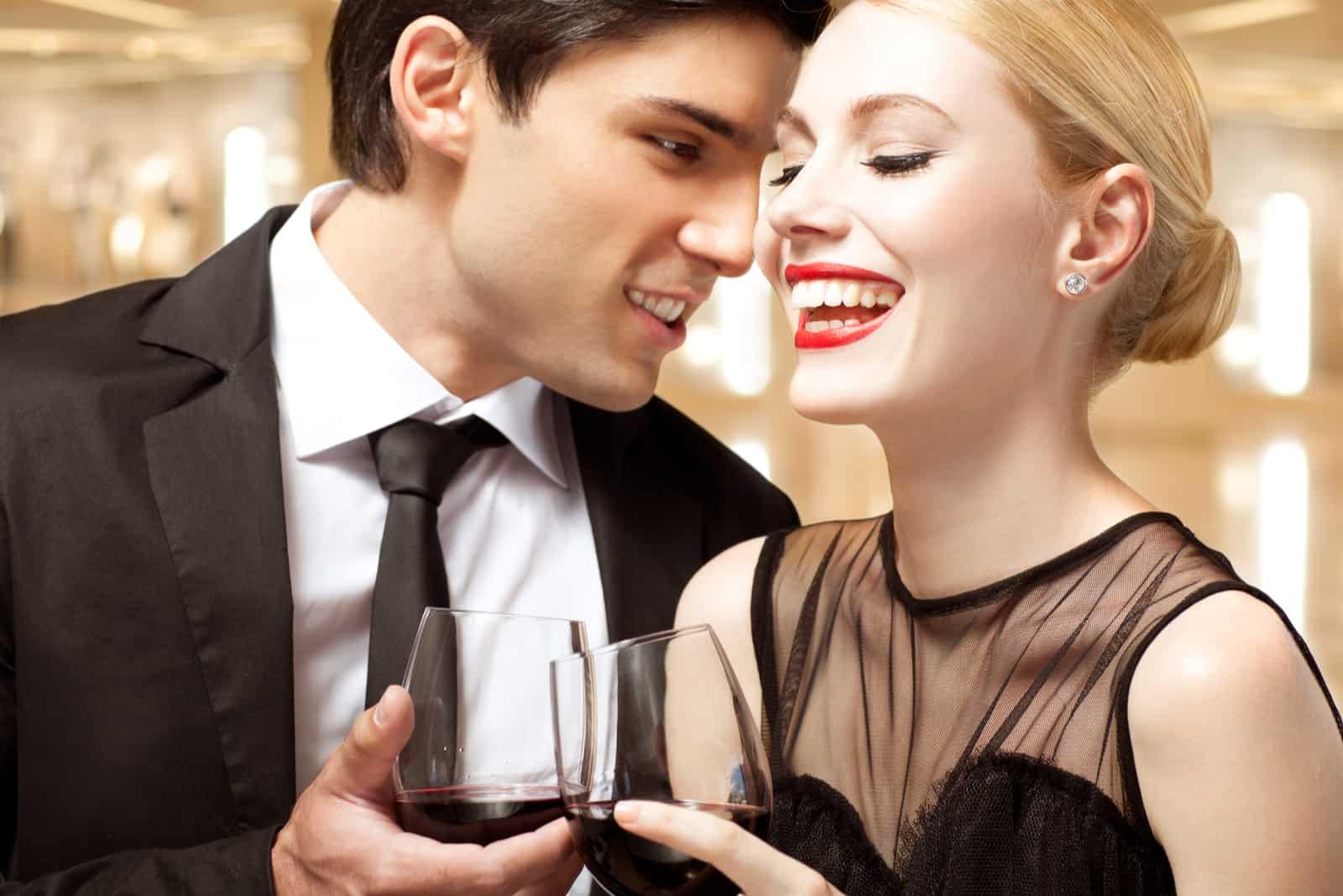 une femme avec une rose rouge boit du vin avec un homme