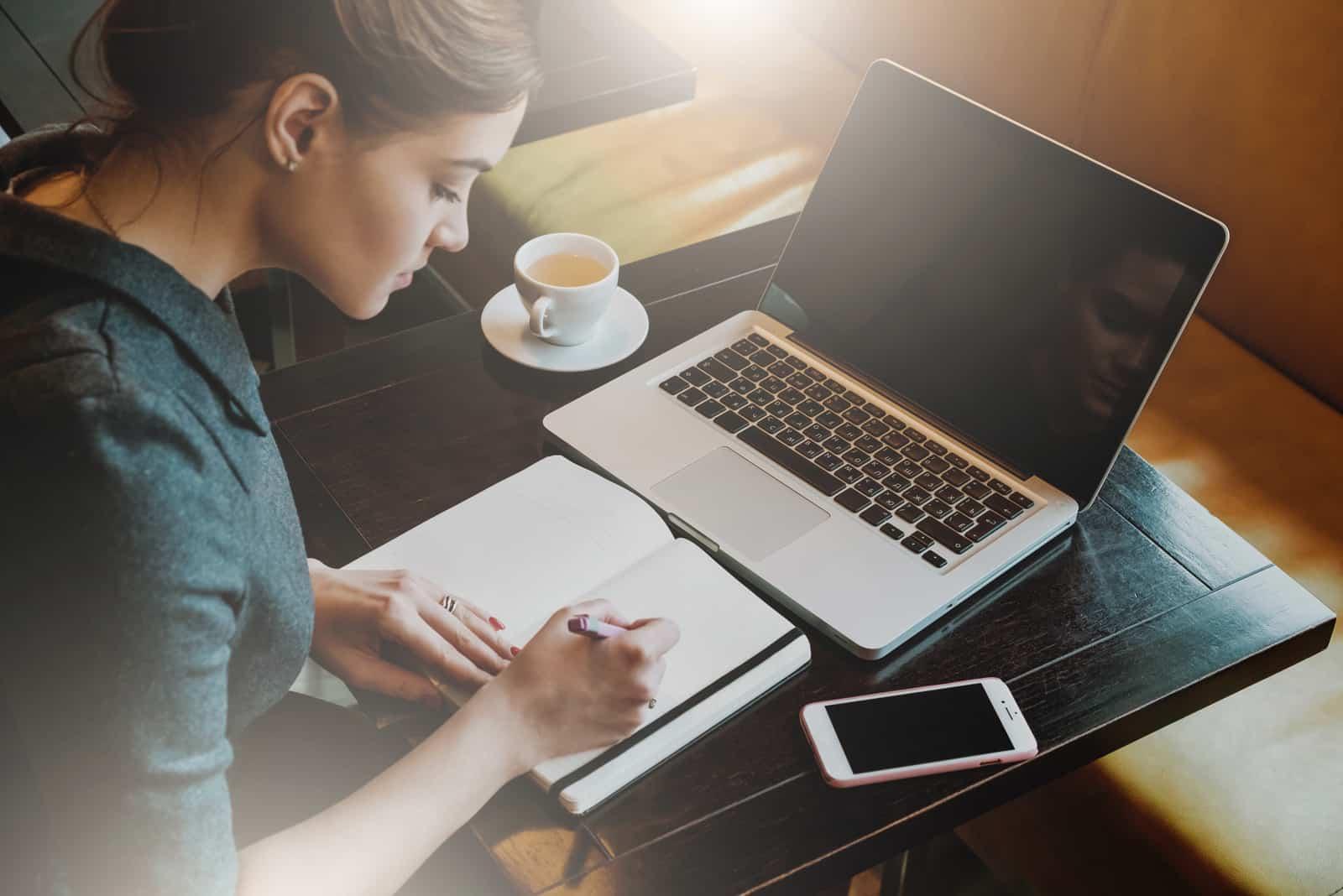 une femme est assise devant un ordinateur portable et écrit