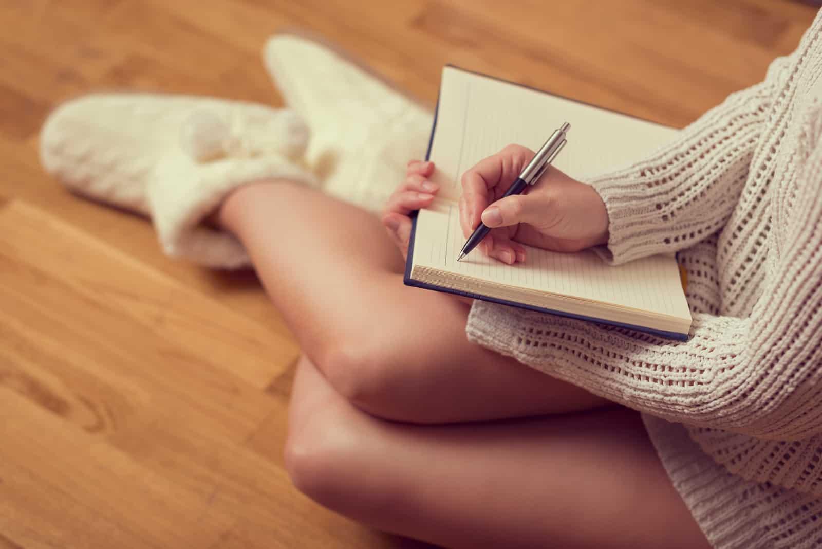 une femme est assise sur le sol et écrit une lettre
