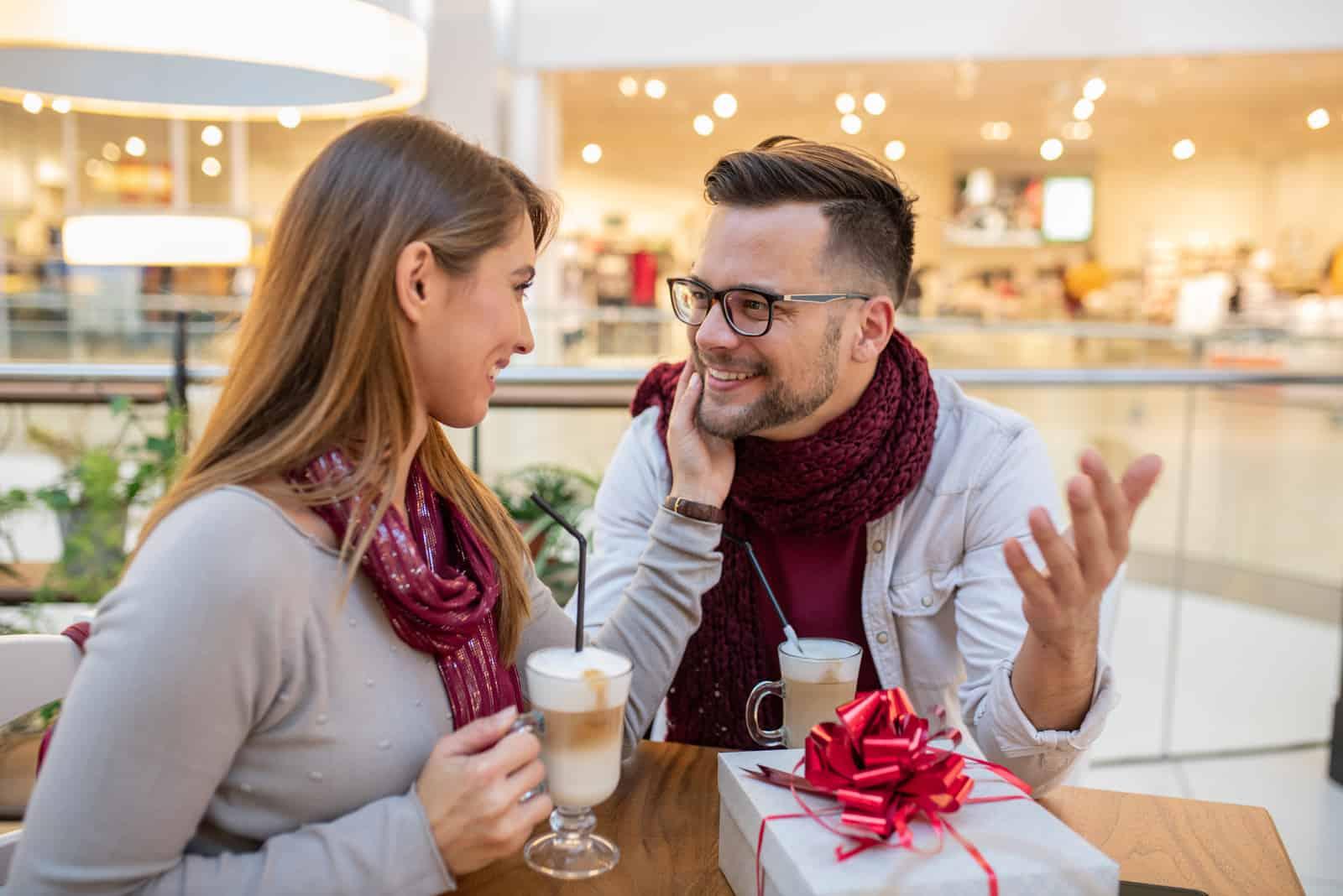 une femme touche un homme en buvant du chocolat chaud