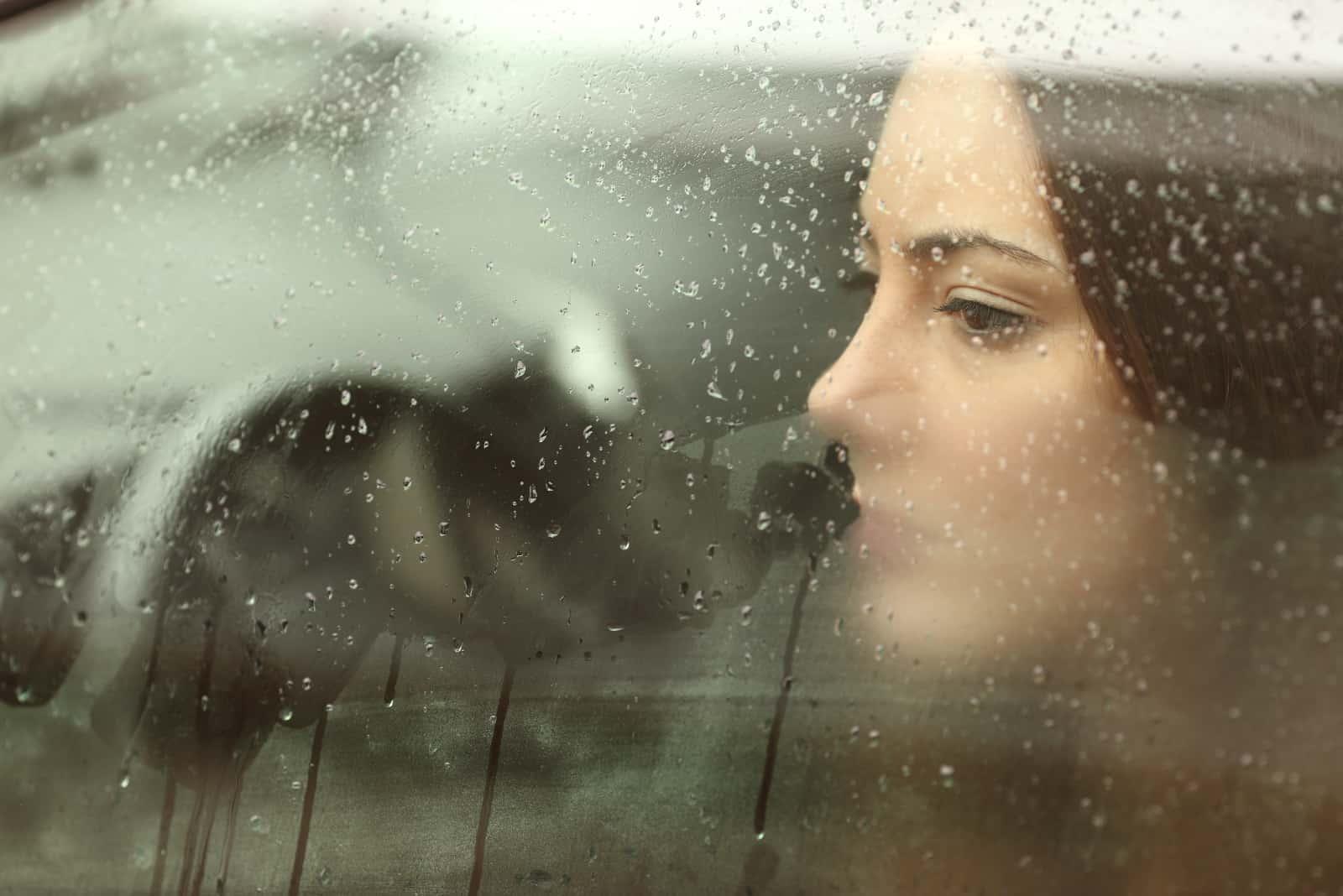 une fille triste regarde par la fenêtre de la voiture