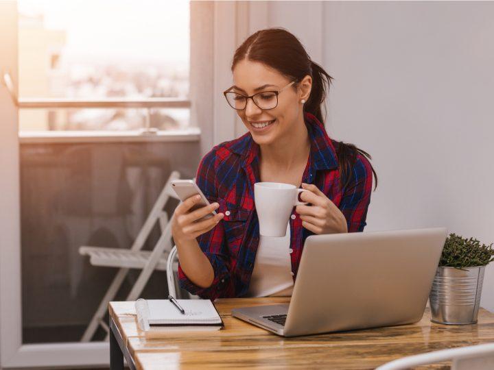 Une femme aux longs cheveux bruns attachés en queue de cheval boit du café et tient un téléphone dans sa main