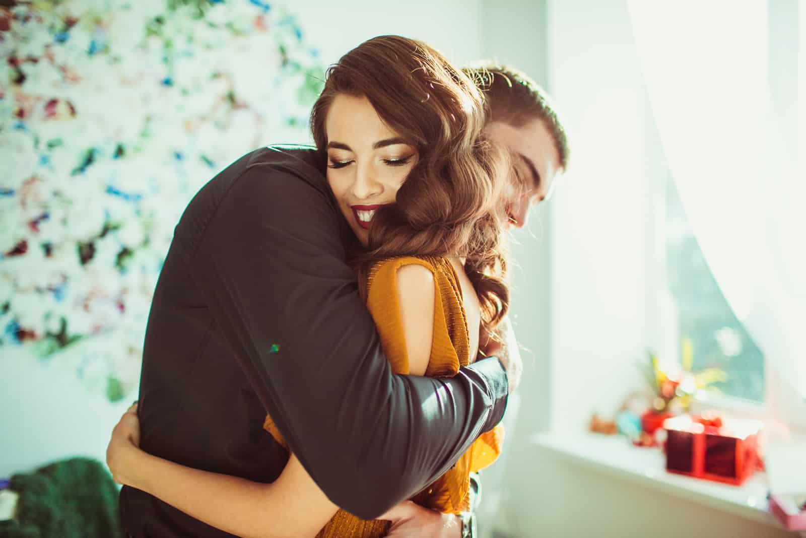 Belle dame se penche sur lépaule de lhomme pendant quil la serre dans ses bras