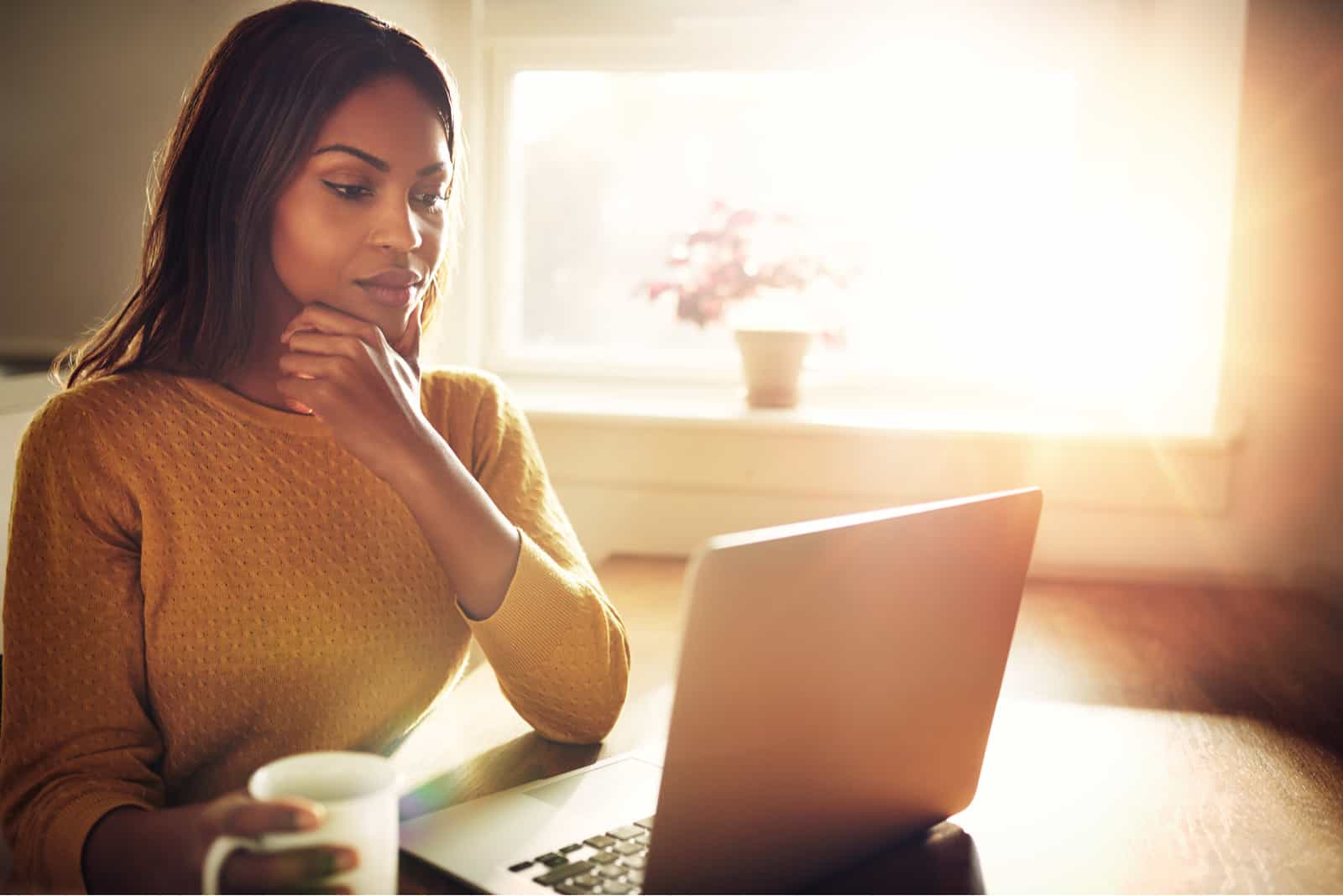 Belle femme avec la main sur le menton assis près de la fenêtre lumineuse tout en regardant un ordinateur portable ouvert