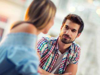 Jeune couple assis dans un café, parler et profiter du premier rendez-vous
