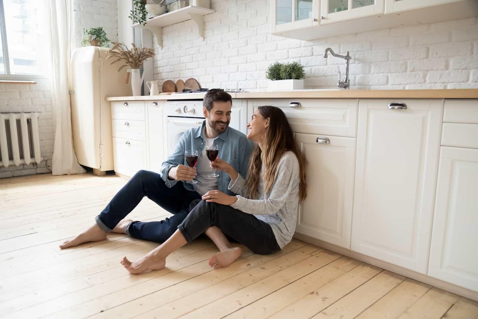 Couple souriant romantique jeune homme et fille assis sur le sol de la cuisine chaude parler tenant des lunettes