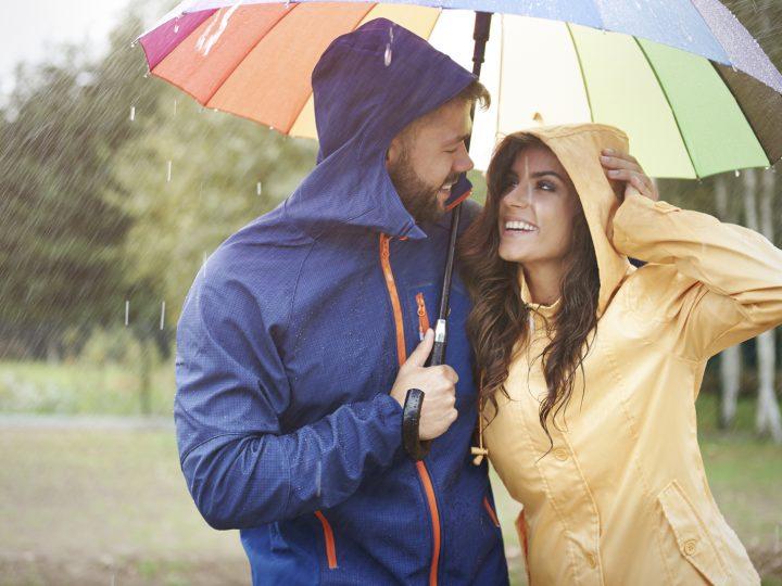 un homme et une femme riant sous des parapluies
