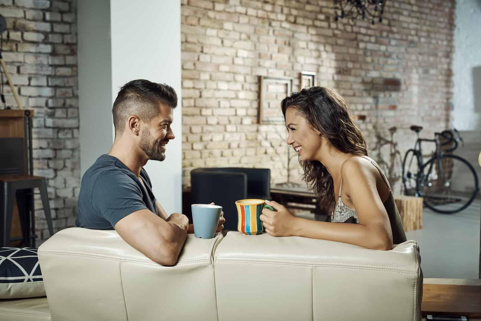 Heureux jeune couple assis sur le canapé