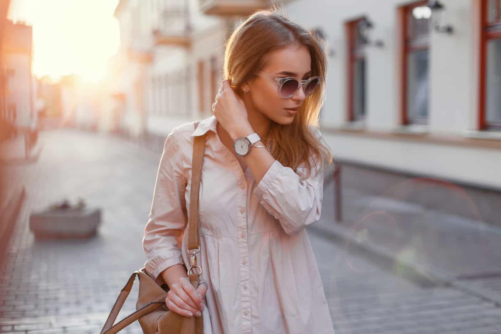 Jeune belle fille dans des lunettes de soleil élégantes et avec un sac à la mode au coucher du soleil.