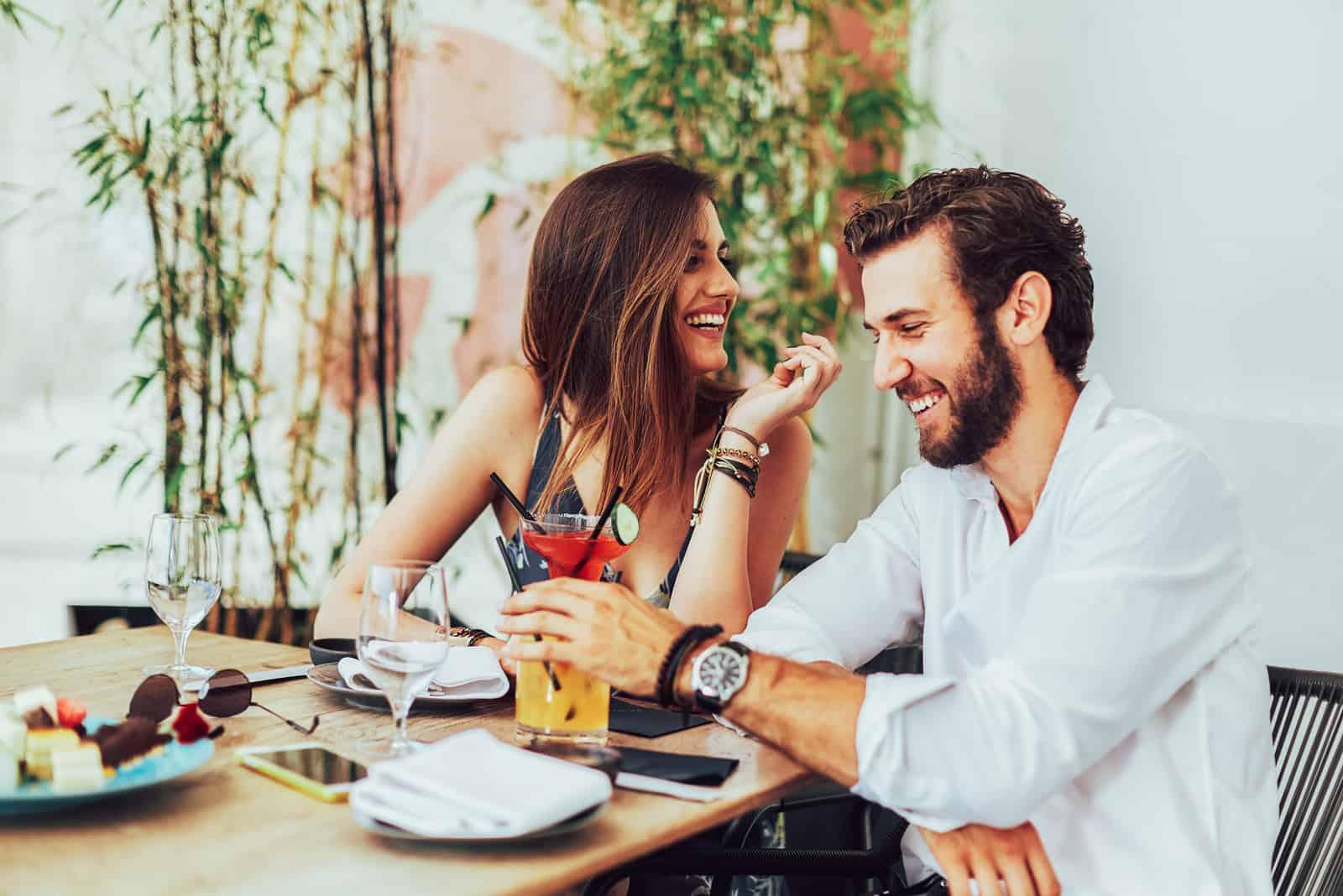 Jeune couple assis dans le bar extérieur et boire des cocktails