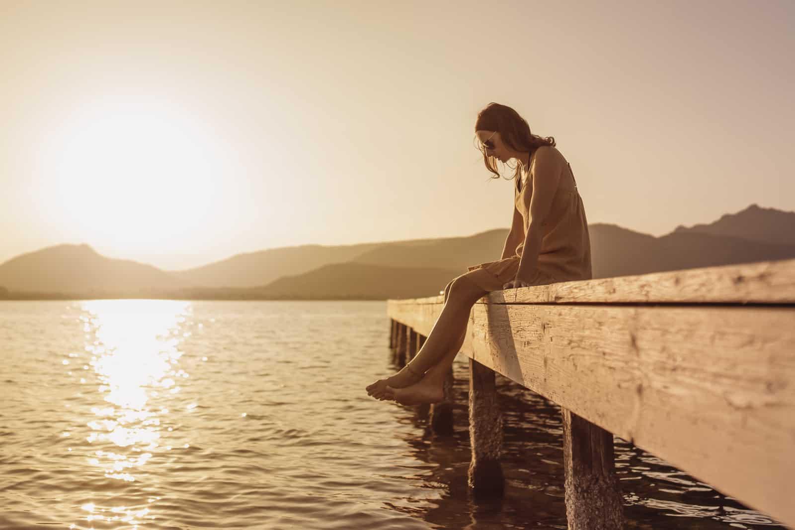 Jolie jeune femme assise sur une jetée dun lac regardant vers le bas