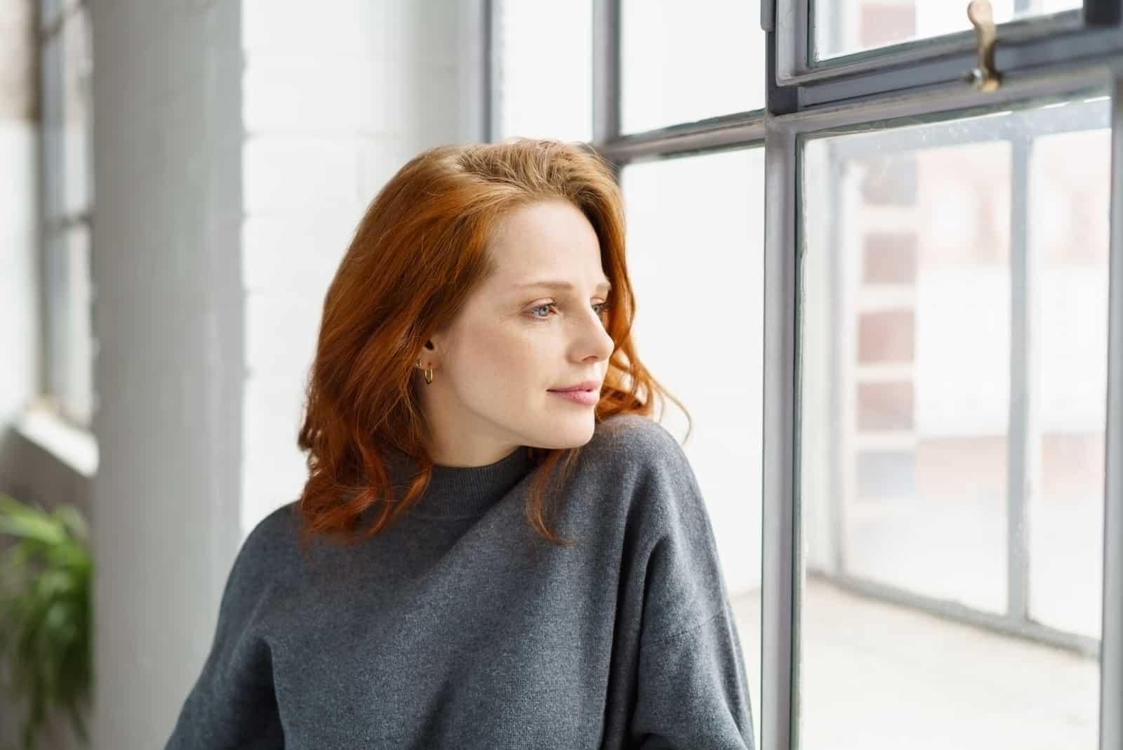 Pensive séduisante jeune femme rousse debout appuyé sur le rebord à regarder par la fenêtre